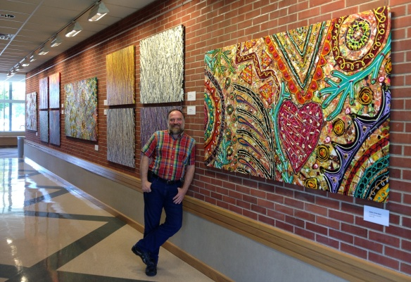 "Robert F Allen with his 4x8 ft 2013 acrylic on canvas, ""Matter of the Heart"" and other paintings in his Manchester University exhibit."